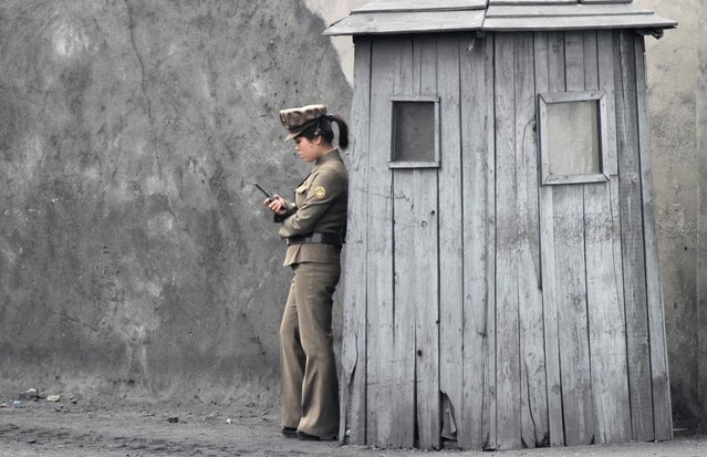 A female North Korean soldier uses her mobile phone next to a sentry on the banks of the Yalu River, near the North Korean town of Sinuiju, opposite the Chinese border city of Dandong June 1, 2014. (Photo by Jacky Chen/Reuters)
