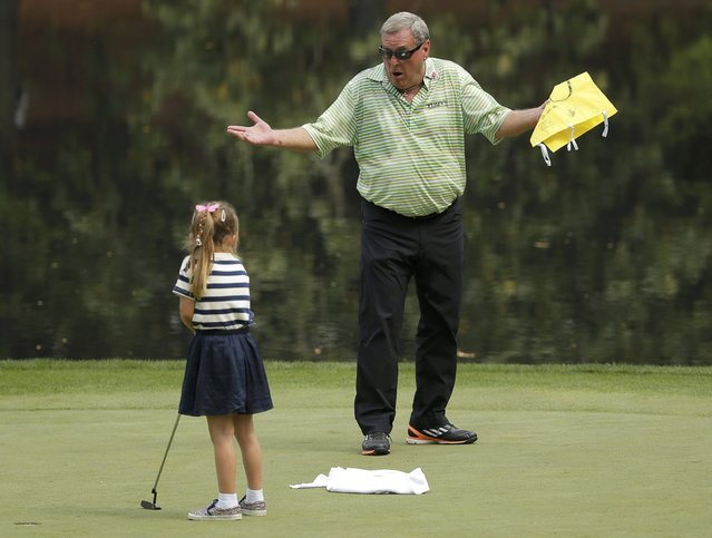 Fuzzy Zoeller of the U.S. reacts as a young girl he pulled from the crowd tries a putt during the par 3 event held ahead of the 2015 Masters at Augusta National Golf Course in Augusta, Georgia April 8, 2015. (Photo by Brian Snyder/Reuters)
