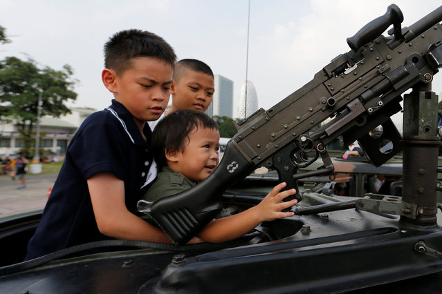 Children play with a weapon on op of an army vehicle during Children's Day celebration at a military facility in Bangkok, Thailand January 14, 2017. (Photo by Jorge Silva/Reuters)