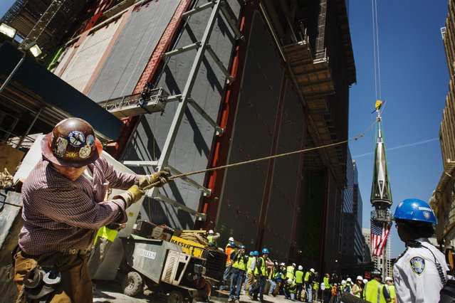 An ironworker uses a line to steady the final piece of a spire, affixed with a U.S. flag, before it is lifted to the top of One World Trade Center in New York, May 2, 2013. (Photo by Lucas Jackson/Reuters)