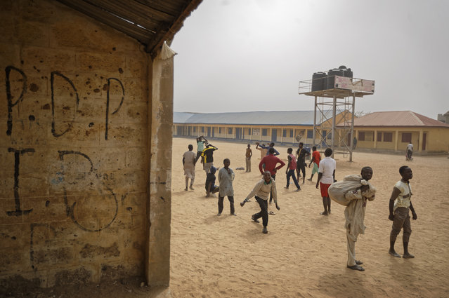 Children play football in the sandy courtyard of Badawa Girls School, on whose wall the initials of the opposition People's Democratic Party have been written, which would have been used as a polling station, in Kano, northern Nigeria, Saturday, February 16, 2019. (Photo by Ben Curtis/AP Photo)