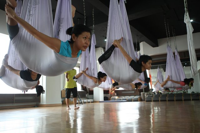 Some women doing yoga pose on the hammocks during the Anti-Gravity yoga class at Svarga e-Motion Sanctuary at Dharmawangsa Square, Jakarta, Saturday, April 18, 2015. (Photo by Jurnasyanto Sukarno/JG Photo)