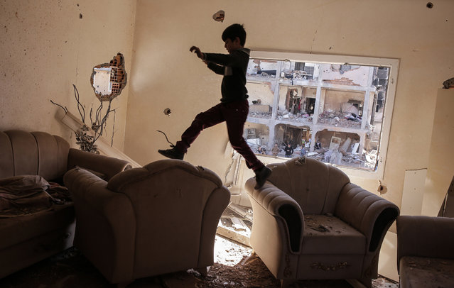 A boy jumps between sofas in his ruined house on March 2, 2016 in Cizre, Turkey. Turkish authorities scaled down a 24-hour curfew imposed on the mainly Kurdish town of Cizre in southeast Turkey, nearly three weeks after declaring the successful conclusion of military operations there. The curfew was lifted at 5 a.m., allowing residents to return to their conflict-stricken neighborhoods for the first time since December 14. But it will remain in effect between 7:30 p.m. and 5 a.m. Residents began trickling back at first light, their vehicles loaded with personal belongings and, in some cases, children. (Photo by Cagdas Erdogan/Getty Images)