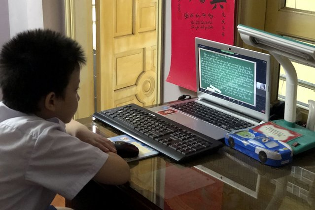 Fourth grader Han Binh Cuong attends a lesson via virtual classroom in Hanoi, Vietnam  Monday, September 6, 2021. Over 20 million Vietnamese students start a new school year on Monday, many of them on virtual classrooms as more than half of the country is in lockdown to contain a COVID-19 surge. (Photo by Binh Huy/AP Photo)