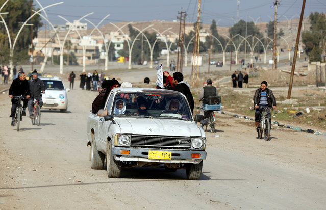 Displaced people who fled the clashes in their area ride in the back of a car to look for a safe place, in the Arabi neighborhood in Mosul, Iraq January 26, 2017. (Photo by Muhammad Hamed/Reuters)