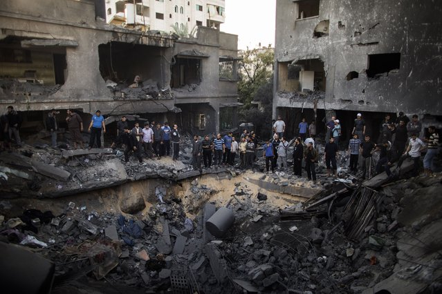 Palestinian men gather around a crater caused by an Israeli air strike on the al-Dallu family's home in Gaza City on November 18, 2012. (Photo by Marco Longari/AFP Photo)