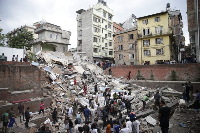 People search for survivors stuck under the rubble of a destroyed building, after an earthquake caused serious damage in Kathmandu, Nepal, 25 April 2015. (Photo by Narendra Shrestha/EPA)
