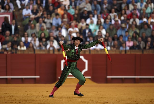 Spanish assistant bullfighter Javier Ambel runs to drive banderillas into a bull during a bullfight at The Maestranza bullring in the Andalusian capital of Seville, southern Spain April 26, 2015. (Photo by Marcelo del Pozo/Reuters)