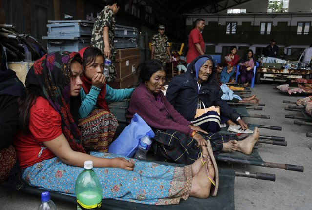 Victims of Saturday's earthquake, sit on stretchers as they wait for ambulances after being evacuated at the airport in Kathmandu, Nepal, Monday, April 27, 2015. (Photo by Altaf Qadri/AP Photo)