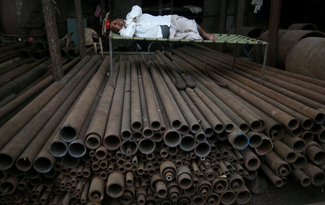 A man sleeps on a bed amidst metal rods in Mumbai, India March 7, 2019. (Photo by Francis Mascarenhas/Reuters)