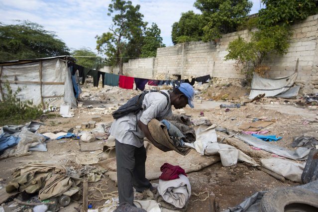 In this December 3, 2016 photo, a man packs his belongings outside his shelter in the Delmas tent camp set up nearly seven years ago for people displaced by the 2010 earthquake, in Port-au-Prince, Haiti. At least 50,000 people remain in some of the settlement camps that emerged in Haiti after the devastating January 2010 earthquake. (Photo by Dieu Nalio Chery/AP Photo)