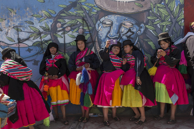 In this January 29, 2017 photo, dancers take selfies after performing during Virgin of Candelaria celebrations in Puno, Peru. The festival of La Candelaria has been celebrated in Puno every year since the 18th century. UNESCO declared the festival a cultural landmark in 2015. (Photo by Rodrigo Abd/AP Photo)