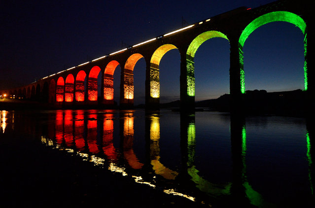 A train travelling on the East Coast mainline is reflected in the River Tweed as it crosses the Royal Border Bridge at dusk, in Berwick-Upon-Tweed in Northumberland, Britain August 22, 2013. (Photo by Toby Melville/Reuters)