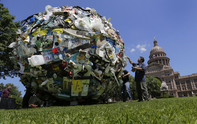 "Workers remove a large ball of trash from the lawn of the Texas Capitol, Wednesday, April 29, 2015, in Austin, Texas. The ball of trash was used as a prop by the Texas Department of Transportation to launch new announcements as part of the ""Don't mess with Texas"" anti-litter campaign. (Photo by Eric Gay/AP Photo)"