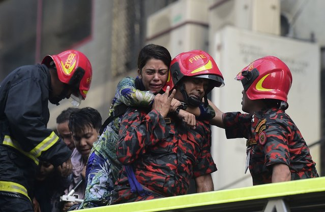 A Bangladeshi survivor reacts after being rescued by firefighters from a burning office building in Dhaka on March 28, 2019. A huge fire tore through a Dhaka office block March 28 killing at least five people with many others feared trapped in the latest major inferno to hit the Bangladesh capital. (Photo by Munir Uz Zaman/AFP Photo)