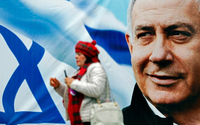 An Israeli woman walks past an electoral billboard bearing a portrait of Israel's Prime Minister Benjamin Netanyahu, in Jerusalem, on April 1, 2019. Israeli general elections will be held on April 9, 2019. (Photo by Thomas Coex/AFP Photo)