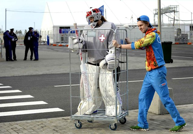 A volunteer transports Switzerland's women Ice Hockey team goalkeeper Florence Schelling to a practice session during the Sochi Winter Olympics on February 9, 2014. (Photo by Alexander Nemenov/AFP Photo)