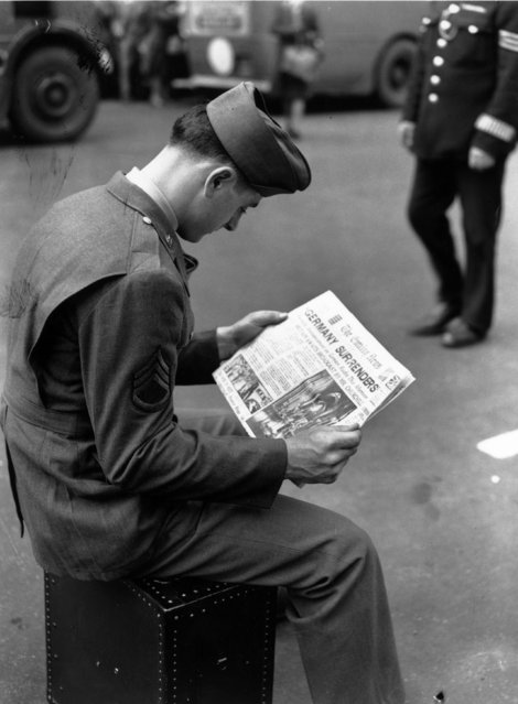 An American soldier in London reads the news of the German surrender at the end of World War II. (Photo by J. Wilds/Getty Images)