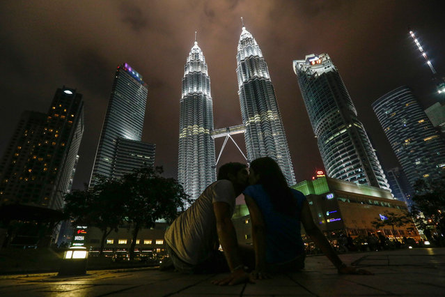 Tourists kissing front of Malaysia's landmark Petronas Twin Towers with lights on before turned off to mark Earth Hour 2016 in Kuala Lumpur, Malaysia, 19 March 2016. Earth Hour takes place worldwide at 8.30 p.m. local time and is a global call to turn off lights for 60 minutes to raise awareness of the danger of global climatic change  (Photo by Fazry Ismail/EPA)