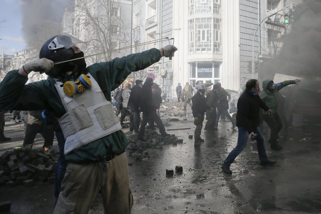 Anti-government protesters clashes with riot police outside Ukraine's parliament in Kiev, Ukraine, Tuesday, Feb. 18, 2014. (Photo by Efrem Lukatsky/AP Photo)