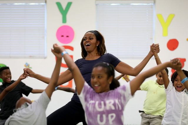 First Lady Michelle Obama participates in a yoga class during a visit to the Gwen Cherry Park NFL/YET Center on February 25, 2014 in Miami, Florida. The visit was part of a celebration around the fourth anniversary of Lets Move!, her initiative to ensure that all our children grow up healthy and reach their full potential. (Photo by Joe Raedle/Getty Images)