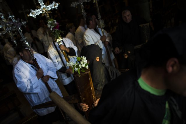 """Masked penitent arrives with his cross to  Roncesvalles Church during spring """"Romeria Cruceros de Arce"""", in Roncesvalles, northern Spain Sunday, May 10, 2015. (Photo by Alvaro Barrientos/AP Photo)"""