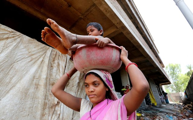 A woman laborer carries her child in a basin on her head near a construction site on the occasion of the International Labour Day or May Day in Bhopal, India on  May 1, 2019. The International Labor Day, commemorates the historic struggle of working people throughout the world. (Photo by Sanjeev Gupta/EPA/EFE/Rex Features/Shutterstock)