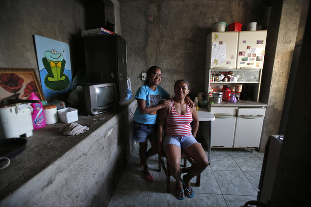 Raimunda Eliandra Alves, 45, poses for a photograph with her daughter Ana Paula Leonardo Justino, 10, at their home at the Pavao-Pavaozinho slum in Rio de Janeiro February 10, 2014. Raimunda is a supermarket cashier who finished her education at age 19. When she was a child, she wanted to become a math teacher when she grew up. She hopes that her daughter Ana Paula will become a veterinarian. Ana Paula says that she will go to high school and then finish college in 2025. (Photo by Sergio Moraes/Reuters)