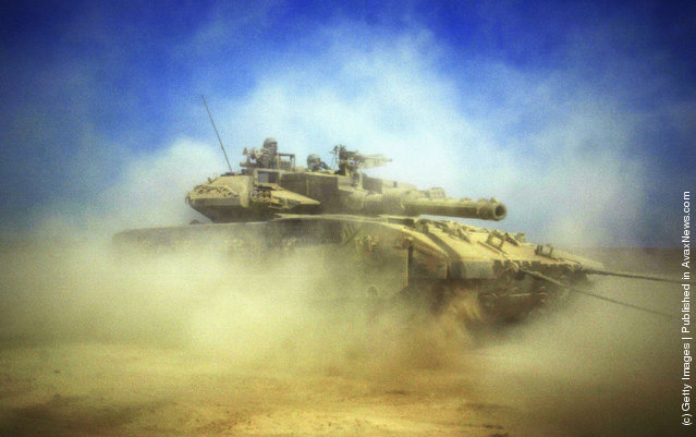 An Israeli tank is pictured at the border between Kibbutz Mefalsim and the Gaza Strip