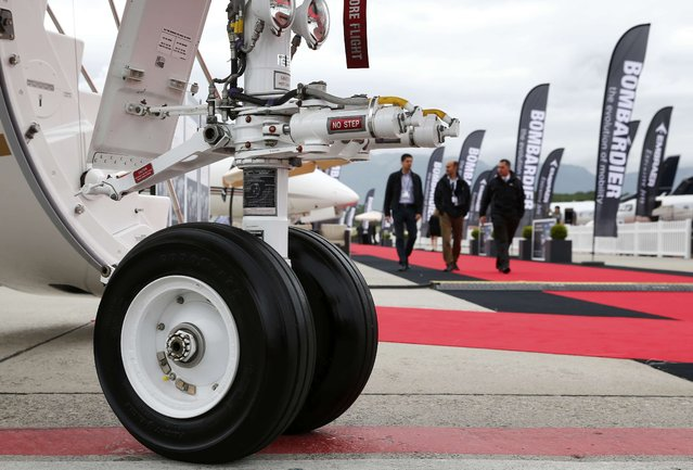 Visitors walk past aircrafts at the static display area during the European Business Aviation Convention & Exhibition (EBACE) at Cointrin airport in Geneva, Switzerland, May 19, 2015. (Photo by Denis Balibouse/Reuters)