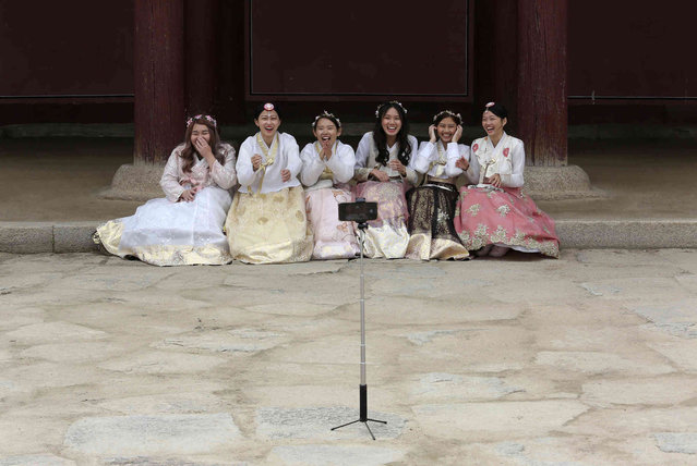 """Visitors, dressed in South Korean traditional """"Hanbok"""" attire, smile to take pictures at the Gyeongbok Palace, the main royal palace in the Joseon Dynasty, in Seoul, South Korea, Wednesday, March 27, 2019. Wearing a """"Hanbok"""", mostly rented, has become a fashionable trend among the youth commonly seen at palaces and other traditional places. (Photo by Ahn Young-joon/AP Photo)"""
