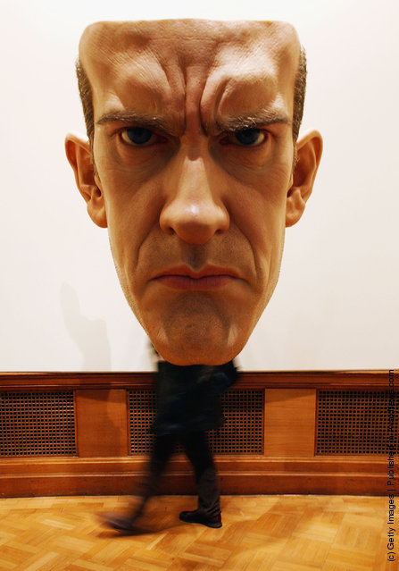 An unidentified man walks behind Ron Mueck's Mask