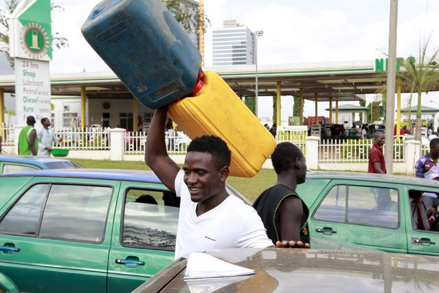 A man carries empty petrol containers outside the NNPC mega petrol station in Abuja, Nigeria May 25, 2015. (Photo by Afolabi Sotunde/Reuters)
