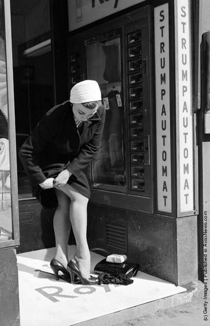 1956: A woman buys a new pair of nylons from a stocking vending machine or automat in Stockholm, and changes into them in a doorway