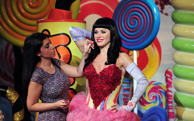 An employee poses with a wax figure of US singer Katy Perry during a photocall at Madame Tussauds in central London on April 2, 2014. (Photo by Carl Court/AFP Photo)