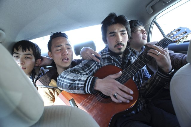 Members of an Afghan band Tanin, Mahmoud Hejran (2nd L) and Zabih Hosseini (C) play the guitar and sing as they travel back to their music studio after performing on a live TV program, in Kabul March 4, 2014. (Photo by Morteza Nikoubazl/Reuters)