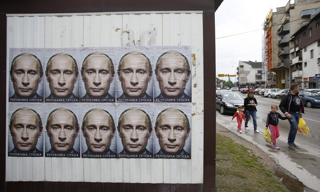 People pass by posters displaying Russian President Vladimir Putin  in the town of Bratunac, near Srebrenica, 150 kms north east of Sarajevo, Sunday, June, 28, 2015. Less than two weeks before the Srebrenica massacre's 20th anniversary, Muslims and Eastern Orthodox Serbs in the Bosnian town are as divided as ever. (Photo by Amel Emric/AP Photo)