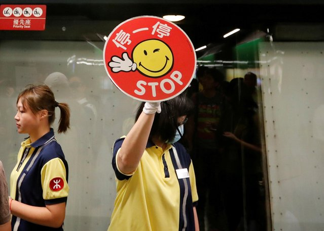 A Mass Transit Railway (MTR) personnel holds up a stop sign towards protesters who are disrupting MTR services at Fortress Hill station in Hong Kong, China August 5, 2019. (Photo by Kim Kyung-Hoon/Reuters)