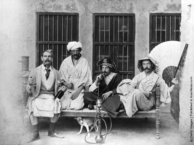 1910:  From left to right: Messrs. Gunning, Thornton, Wood and Garden relaxing in Bustine, Persia. Mr Wood is smoking a hookah pipe
