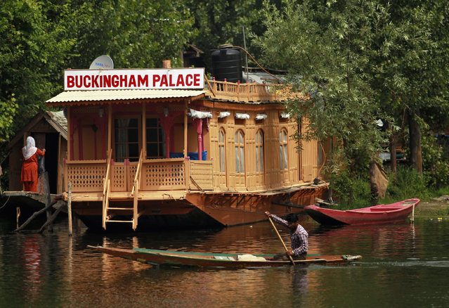 "A Kashmiri man rows a Shikara in front of a houseboat named ""Buckingham Palace"" on the waters of Dal Lake in Srinagar June 13, 2012. (Photo by Fayaz Kabli/Reuters)"