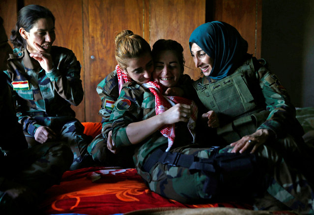 Yazidi female fighter Asema Dahir (L), 21, jokes with her comrades in a bedroom at a site near the frontline of the fight against Islamic State militants in Nawaran near Mosul, Iraq, April 20, 2016. (Photo by Ahmed Jadallah/Reuters)