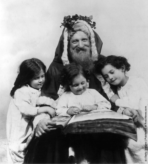 1915: Father Christmas reading with three young children
