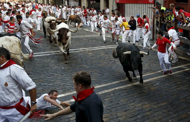 A runner falls next to a Jandilla fighting bull (R) as another Jandilla bull charges at a runner (background) at the Mercaderes curve during the first running of the bulls of the San Fermin festival in Pamplona, northern Spain, July 7, 2015. (Photo by Susana Vera/Reuters)