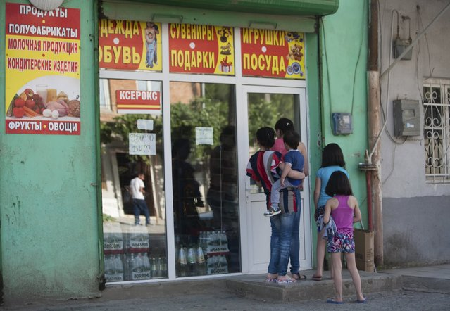 People gather near a shop, with bottles of Borjomi bottled mineral water seen behind a window, in Leningori (or Akhalgori), in the breakaway region of South Ossetia, Georgia, July 6, 2015. (Photo by Kazbek Basaev/Reuters)