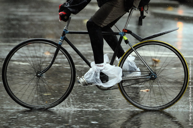 A man covers his shoes with plastic carrier bags as he cycles through the pouring rain on January in London