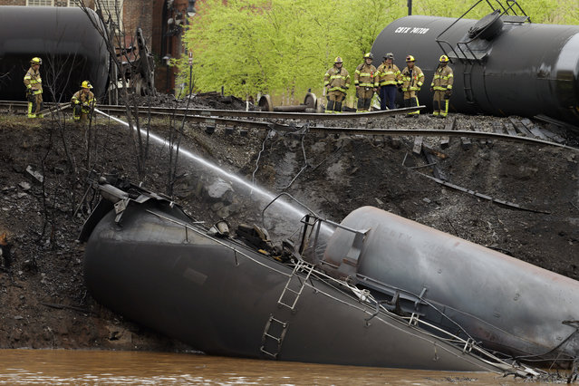 Firefighters and rescue workers work along the tracks where several CSX tanker cars carrying crude oil derailed and caught fire along the James River near downtown in Lynchburg, Va., Wednesday, April 30, 2014. Police said that more than a dozen tanker cars were involved in the derailment. (Photo by Steve Helber/AP Photo)