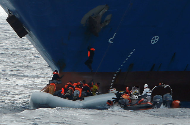 Migrants in a rubber dinghy fall into the sea alongside a rigid hulled inflatable boat (RHIB) of the Malta-based NGO Migrant Offshore Aid Station, as a migrant climbs onto the anchor of the Panama-registered ship Tuna 1 and one hangs onto its bow, after some 20 migrants on another rubber dinghy drowned in the central Mediterranean in international waters off the coast of Libya, April 16, 2017. (Photo by Darrin Zammit Lupi/Reuters)