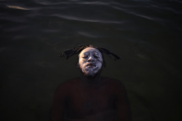 Portrait in Guanabara Bay by Fabio Teixeira, Brazil: a young African refugee from the Democratic Republic of Congo floating in the waters of Guanabara Bay, Ramos Beach. Second place – people in nature. (Photo by Fabio Teixeira/The Nature Conservancy Global Photo Contest 2019)