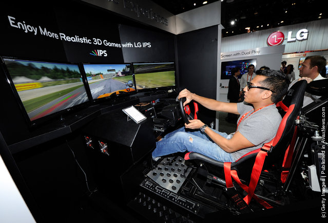 Sujhon Das of Nevada plays the 'Need for Speed: Shift' racing video game using a racing motion machine and LG Cinema 3D IPS TVs at the LG Electronics booth at the 2012 International Consumer Electronics Show