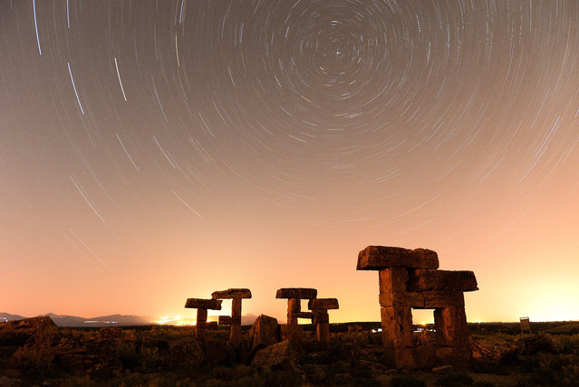 Long exposure of starlight trails in the night sky over the ruins at Blaundus ancient city at night in Ulubey district of Turkey`s Usak on July 03, 2019. Astronomy photographers frequently visit the ancient city of Blaundus, located on a peninsula surrounded by deep valleys. The city was established by Macedonians who came to the region after Alexander the Great's Anatolian expedition. Later the city was ruled by the Pergamon Kingdom and the Roman Empire. Entrance gate of the city, horses, and arches symbolizing the city are among the historical buildings in the region. The buildings in the ancient city offer different visuals on day and night. (Photo by Soner Kilinc/Anadolu Agency/Getty Images)